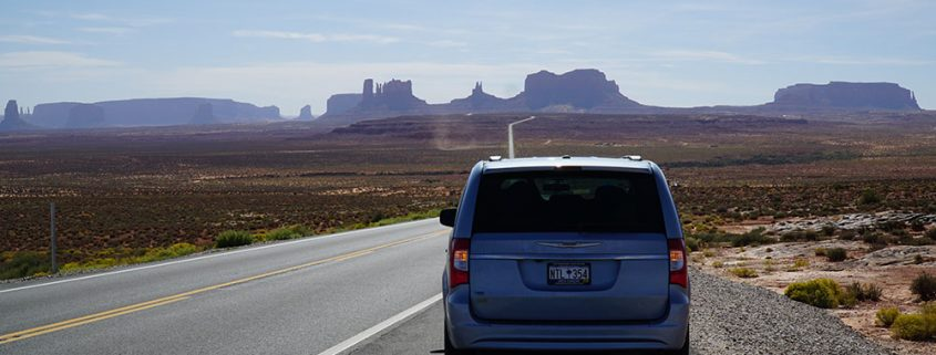 Our car with Monument Valley in the distance, near the Arizona-Utah border