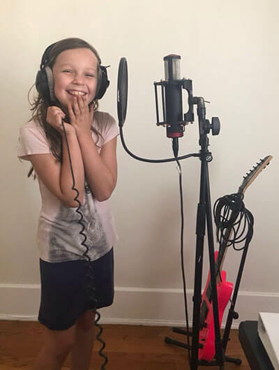 Picture of girl recording a song at a microphone